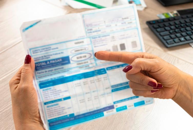 Una colombiano mirando una factura de uno de sus servicios públicos