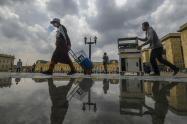 Vendedores ambulantes con tapabocas caminan en la plaza Bolívar, en Bogotá.
