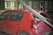 Poste cae sobre carro