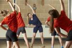 Niños haciendo ejercicio con supervisión de un preparador físico