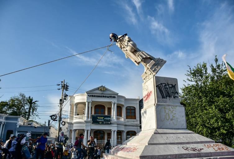 Manifestantes derriban estatua de Cristobal Colon.