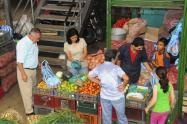 Consumidores en un mercado comprando productos básicos de la canasta familiar
