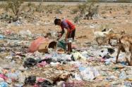 Niño indígena buscando alimentos entre la basura.
