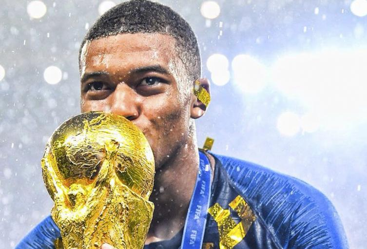 Kylian Mbappé besando la Copa del Mundo